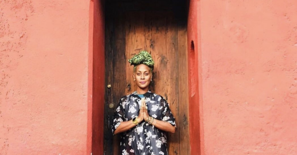 picture of a yoga teacher inside of a red doorway with wood behind her and her hands together in front of her heart looking at the camera